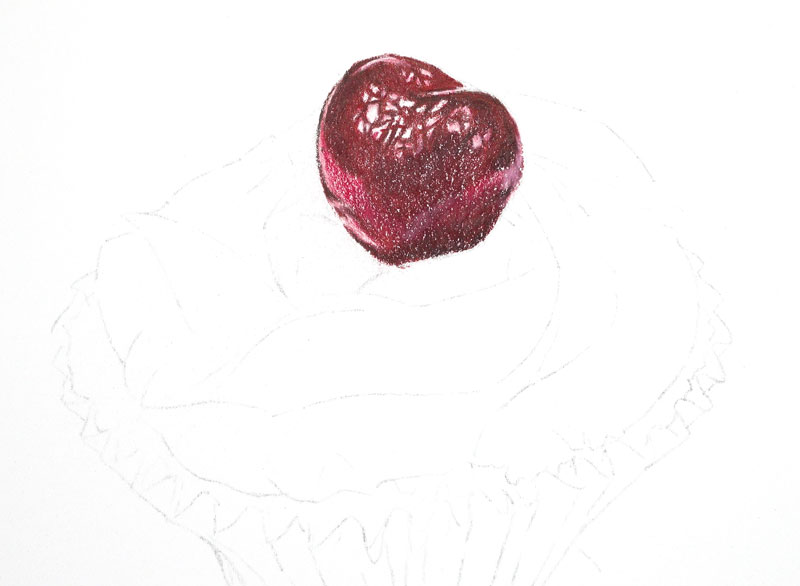 Colored pencil applications on the cherry on top of the cupcake